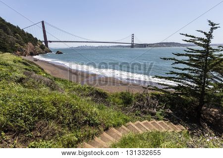 San Francisco Bay hiking trail and beach cove with view through Golden Gate Bridge in Golden Gate National Recreation Area.