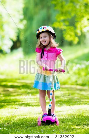 Little child learning to ride a scooter in a city park on sunny summer day. Cute preschooler girl in safety helmet riding a roller. Kids play outdoors. Active leisure and outdoor sport for children.
