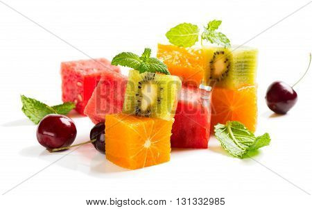 Watermelon cherry kiwi orange and leaves of mint consisting of a fruit salad isolated on a white background.