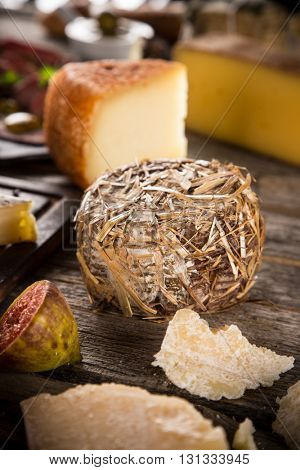 Delicious various cheeses on old wooden table