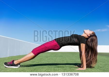 Yoga fitness woman stretching body in upward plank pose doing reverse planking exercise on outdoor grass park. Sport woman strength training her core body with bodyweight flexibility exercises.