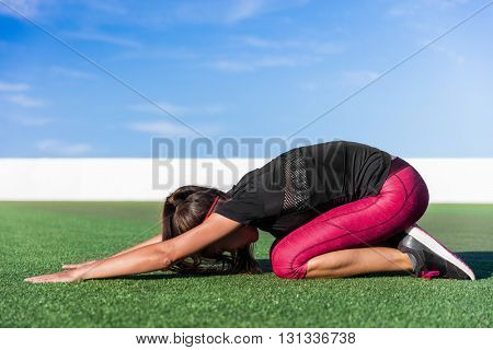 Yoga Asian woman doing back stretches stretching exercises named childs pose stretch with extended arms for health and body flexibility on grass floor of summer outdoor fitness gym.