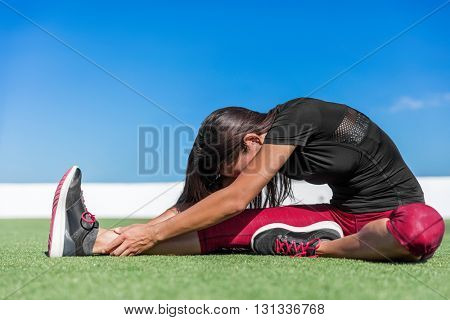 Fitness woman stretching back and leg muscles with toe-touch stretches. Sporty young athlete doing a one leg seated forward bend yoga stretch on outdoor grass. Sitting head to knee fold over pose.