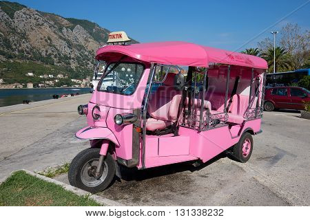 KOTOR MONTENEGRO - SEPTEMBER 23 2015 : Pink auto rickshaw or tuk-tuk on the street of Kotor. Tuk tuks are commonly used in transporting tourists. This transport is very popular in Thailand and India