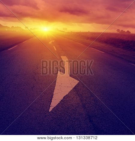 Country road with arrow sign on asphalt at sunset. Vintage style.