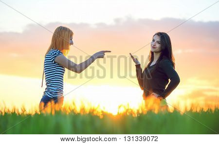 Two girls arguing pointing a finger and ignoring