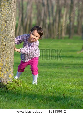 Little girl hiding behind a tree in a forest