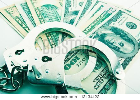 Silver handcuff and dollar bank notes