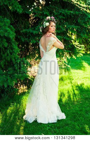 Portrait of beautiful brunette  bride  in a luxurious wedding dress with bouquet outdoors. Bride with long healthy hair in flower wreath. Wedding makeup, wedding hairstyle. summer portrait.