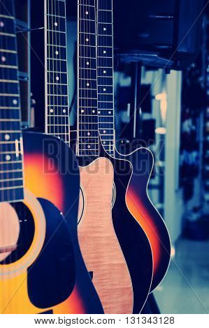Colorful acoustic guitars in the store background