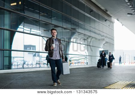 man in airport holding a bag and walking with cup of coffee.