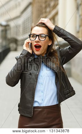 Pretty surprised businesswoman walking down the street while talking on smart phone