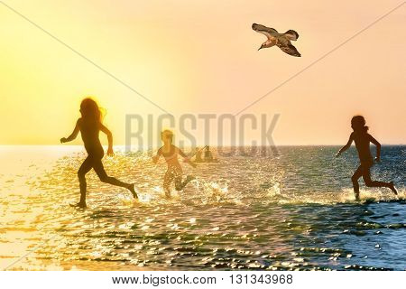 Silhouettes of children running through the water at scenic sunset backlit
