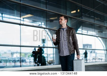 Portrait of a young man walking near the airport with suitcase and cup of coffee.