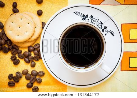 A cup of black coffee, crackers and coffee beans on a bright orange tablecloth