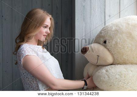 Beautiful girl hugging a teddy bear. Blonde woman posing in the studio