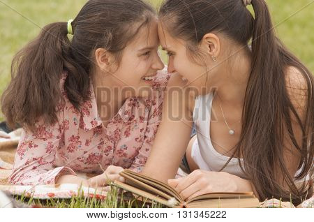 smiling mother and daughter lying on the grass and lookin at each other
