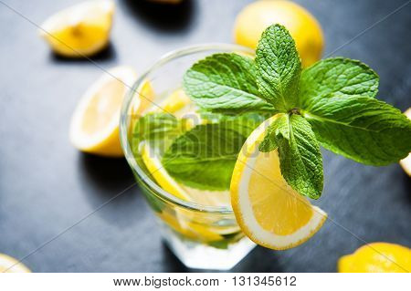 Refreshing cold lemonade Cocktail on dark stone table. Top view