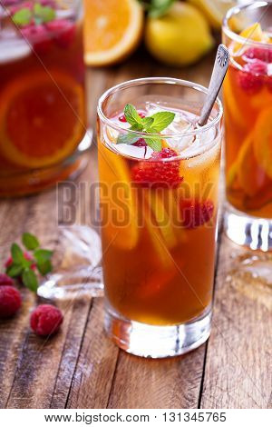 Iced tea with orange and raspberry in tall glasses on rustic background