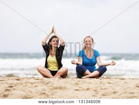 Two smiling young women sitting and relax in lotus pose outdoors. Two happy girls sitting outdoors. Selective focus on the models.