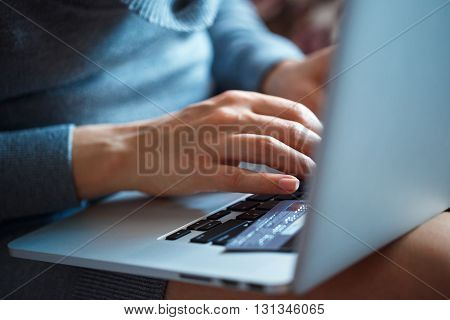 Hands using laptop and credit card on it. Online shopping