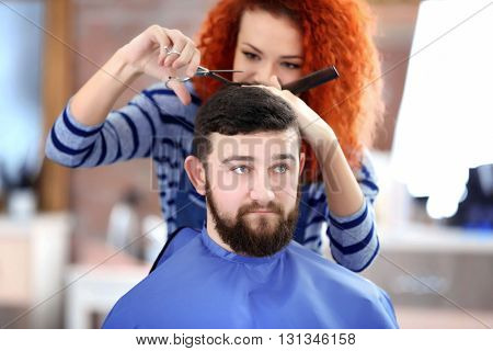 Professional hairdresser making new haircut  her handsome client