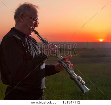 musician, trumpeter playing the instrument at sunset