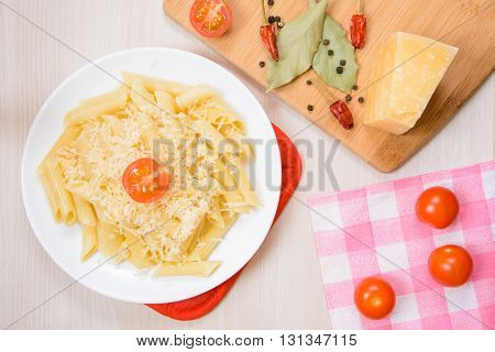 Penne pasta with grated cheese on a white round plate next to the spices and tomatoes on the table. Top view.