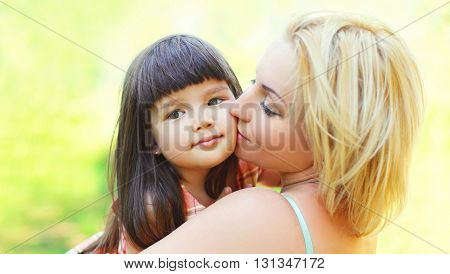 Portrait happy loving mother kissing child outdoors in summer sunny day
