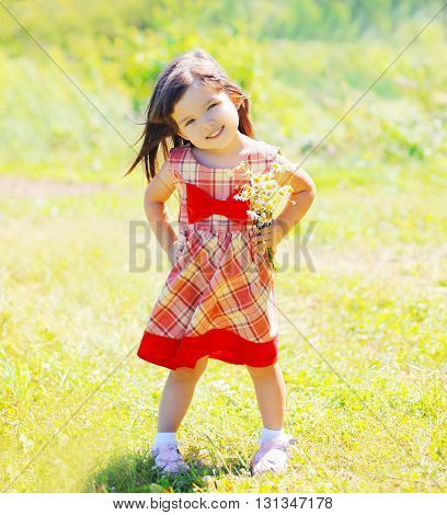 Little Girl Child With Flowers Outdoors In Summer Day