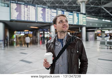 Smiling thoughtful man at board of arrivals and departures at the airport with a cup of coffee.