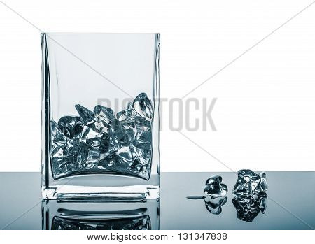 Empty glass with ice cubes on the mirror surface. Painted image isolated on the white background.