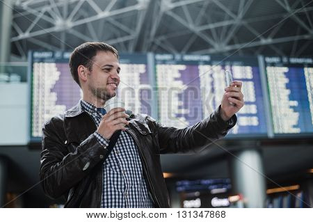 Smiling young traveller man at the airport makes selfie in front of timetable board.