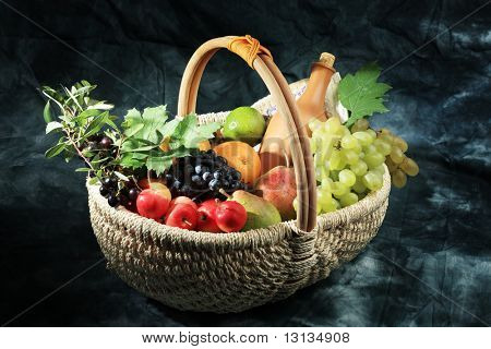 Beeren und Wein Komposition in einen Korb.