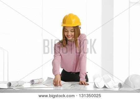 Young beautiful female construction engineer working in the office