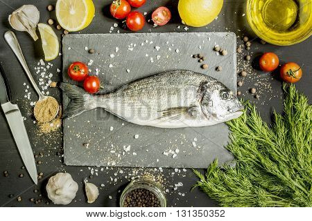 dorado fish with vegetables and a number of spices on a dark surface during cooking