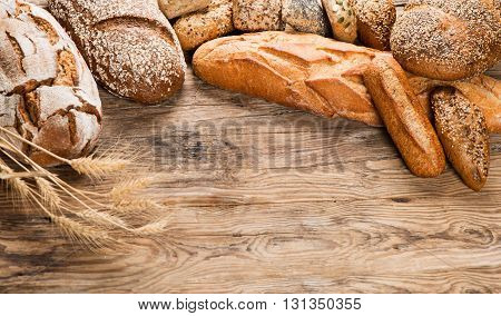 Variety of bread and ears of wheat on wooden background with space for text.