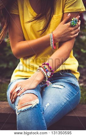 young woman in blue jeans and yellow t-shirt focus on hand with colorful bracelets