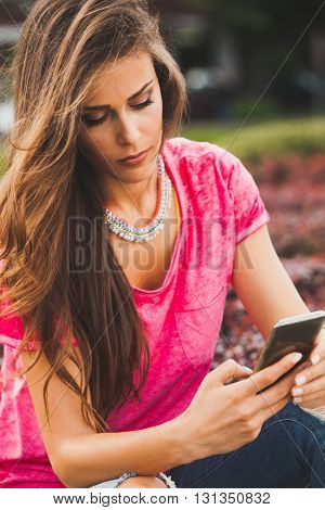 young urban woman with smartphone outdoor summer day shot closeup