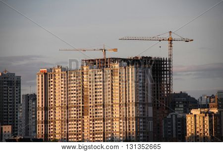 Construction cranes works over modern housing complex