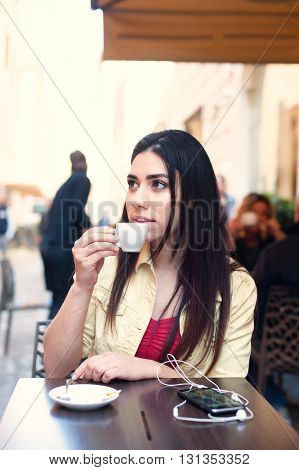 Young woman drinking in coffee bar outdoor in city street sitting at table spring time