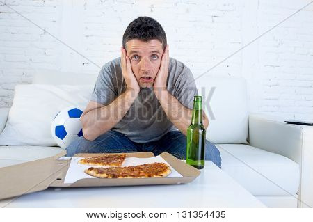 young man alone holding ball in stress watching football game on television sitting at home living room sofa couch with pizza box and beer bottle enjoying the match looking nervous and excited