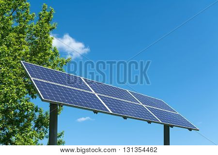 Large solar panel against a blue sky and trees