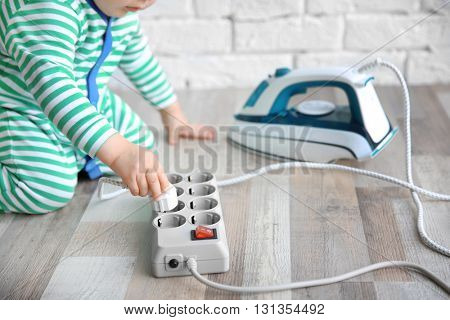 Little child playing with iron and electric power bar at home