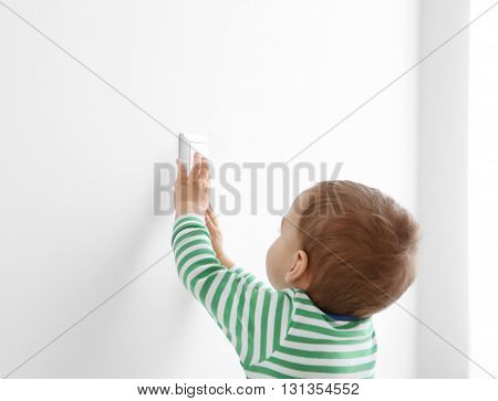 Little child playing with switch