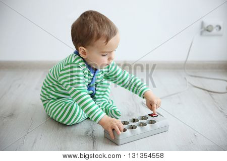 Little baby playing with electric power bar