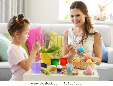 Mother and daughter decorating Easter eggs indoors