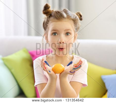 Cute little girl holding Easter egg indoors