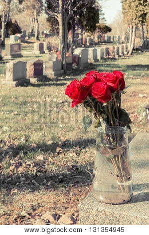 Bouquet Of Red Roses In A Vase In A Cemetery, With A Fading Retro Effect