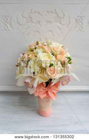 Beauty of colored flowers. Bridal accessories. Close-up bunch of florets. Details for marriage and for married couple. Wedding bouquet with tender orchids, roses on the white background